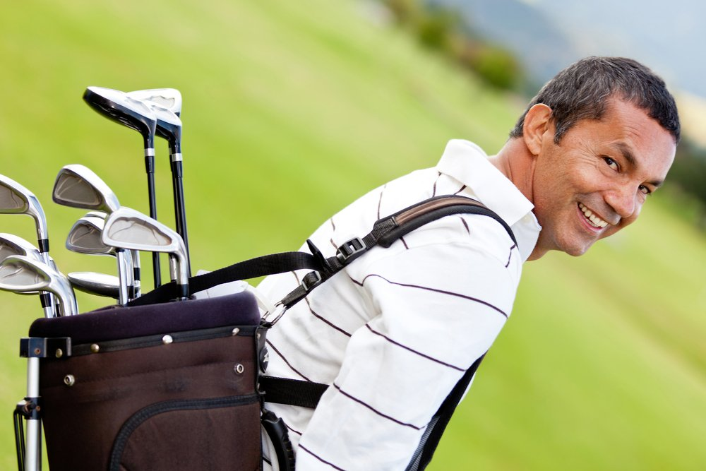 Man at the course carrying a golf bag